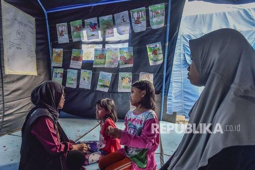 Relawan melakukan Trauma Healing dengan cara mengajak bermain anak-anak korban gempa tsunami Palu di kantor Dinas Sosial, Palu, Sulawesi Tengah, Jumat (5/10).