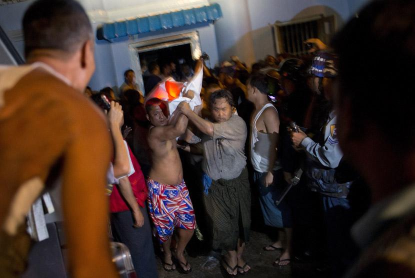 Relawan membawa kantong mayat, yang berisi jenazah korban kebakaran sebuah masjid di Yangon, Myanmar, Selasa,Selasa (2/4). (AP/Gemunu Amarasinghe)