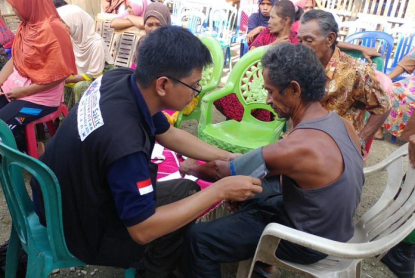 RelawanRumah Sakit Umum Universitas Muhammadiyah Malang (RSU UMM) tengah mengobati salah satu korban bencana di Sulawesi Tengah.