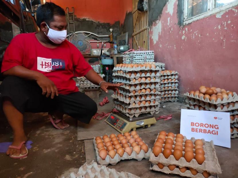 """Relawan Rumah Zakat Desa Berdaya Bojongsari, Muhammad Toha, melaksanakan kegiatan """"Borong Berbagi"""", Kamis (16/9). Dalam kegiatan berbagi ini, relawan memborong 30 kg telur yang dijual oleh Saptari."""