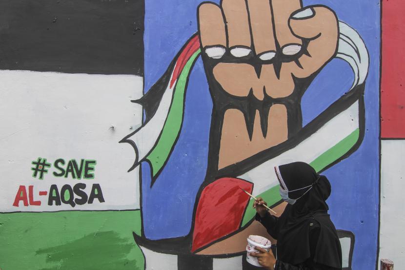 Remaja menyelesaikan pembuatan mural bertema solidaritas Palestina di Gang Jambu, Kedaung, Depok, Jawa Barat, Selasa (18/5/2021). Remaja Majelis Al Muntaqilin membuat Mural tersebut sebagai aksi solidaritas serta doa bagi umat muslim Palestina dan Masjid Al Aqsa terhadap serangan pasukan Israel.
