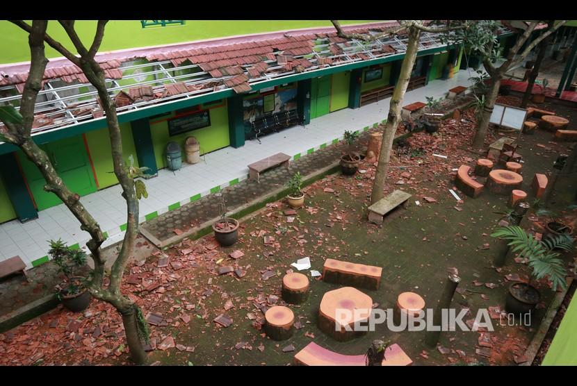 Reruntuhan genting sekolah terlihat memenuhi halaman sekolah yang rusak akibat gempa di SMK Negeri 1 Turen, Malang, Jawa Timur, Sabtu (10/4/2021). Gempa yang mengguncang kawasan Malang dan sekitarnya membuat sejumlah bangunan rusak.