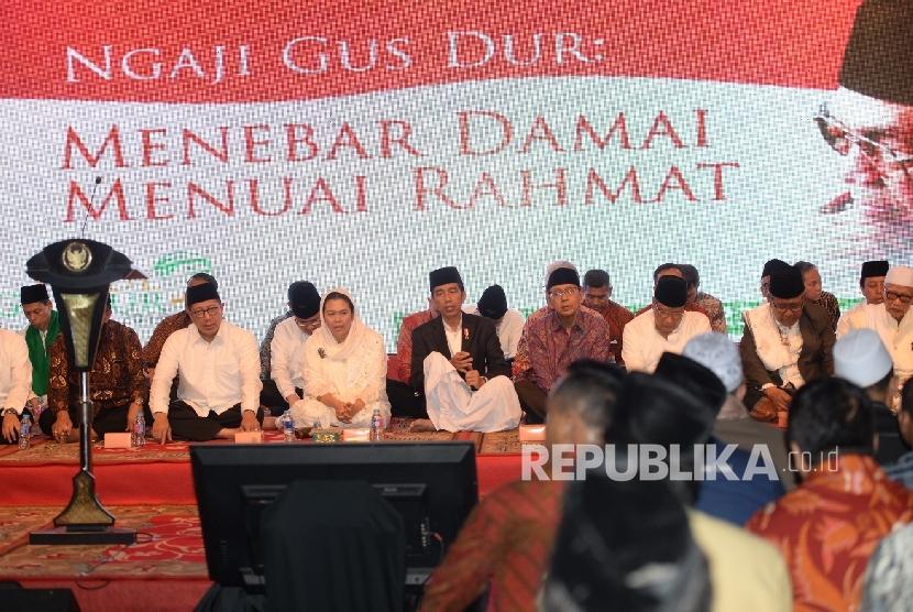 Presiden Joko Widodo (tengah) bersama Yenny Wahid (kiri) dan mantan Wapres Boediono saat Haul Gus Dur ke-7 di Jakarta, Jumat (23/12). Pada Haul ke-7 Gus Dur ini mengangkat tema Menebar Damai Menuai Rahmat. Republika/ Wihdan Ikrar Ciganjur.