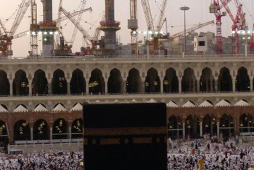 Ribuan umat muslim beribadah di Masjidil Haram, Mekkah, Arab Saudi, dengan latar belakang proyek pembangunan perluasan Masjidil Haram, Selasa (4/10). Pemerintah Arab Saudi melakukan perluasan pelataran sebelah utara Masjidil Haram hingga 400 ribu meter yan