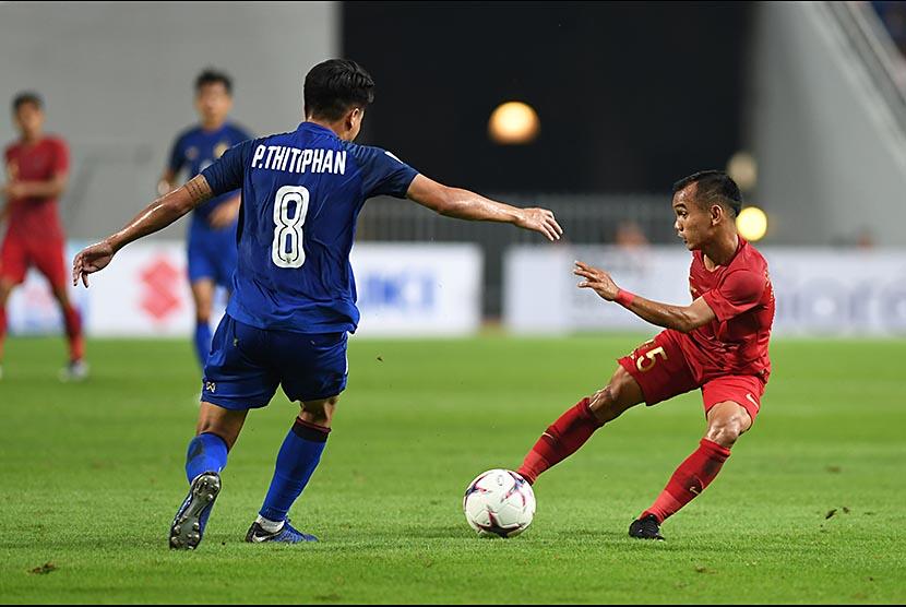 Riko Simanjuntak (kanan) menggocek bola dari sergapan bek Thailand Thitiphan Puangjan (kiri) dalam laga lanjutan Piala AFF 2018 di Stadion Nasional Rajamangala, Bangkok, Thailand, Sabtu (17/11)