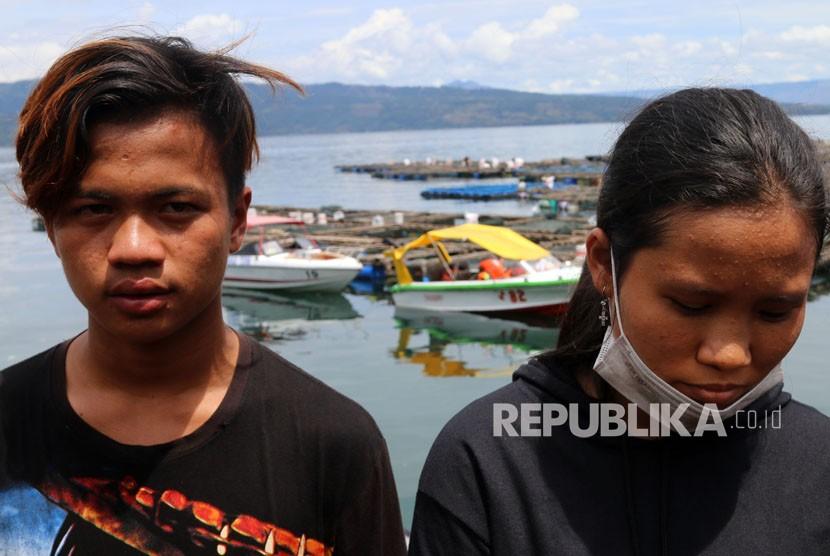 Roni Siadari (kiri) dan Tiambun Syahnia (kanan) dua penumpang KM Sinar Bangun yang selamat, berdiri di kawasan dermaga Tigaras, Danau Toba, di Simalungun, Sumatera Utara, Ahad (24/6).