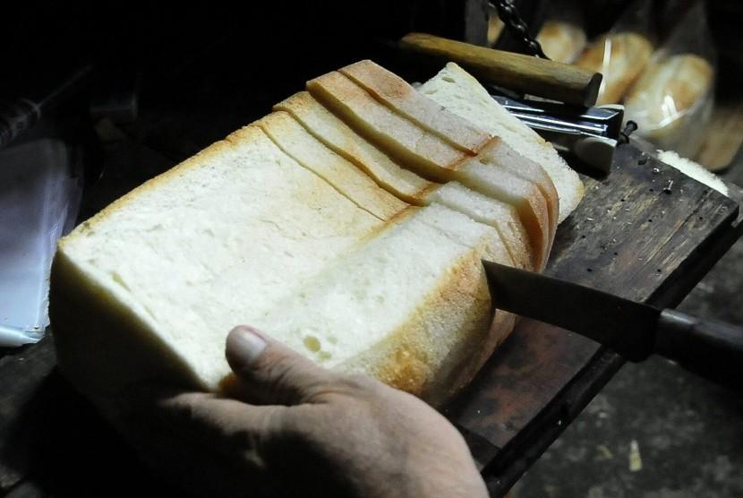 Roti tawar sedang dipotong.