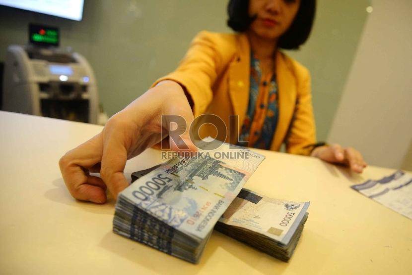 Rupiah Semakin Melemah: Teller melakukan transaksi dengan nasabah di Banking Hall Bank Mandiri, Jakarta, Rabu (11/3).