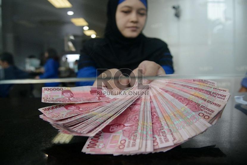 Rupiah Terus Merosot: Petugas menghitung uang rupiah dan dolar di salah satu penukaran uang di Jakarta, Kamis (5/3).