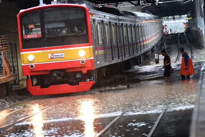 Salah satu rangkaian KRL Commuterline melintas perlahan pada jalur rel yang terendam banjir di Stasiun KA Sudirman, Menteng, Jakarta, Rabu (1/1/2020). Banjir yang menggenangi sejumlah titik pada jalur rel di Jakarta berdampak pada gangguan pelayanan sejumlah rute KRL Commuterline Jabodetabek.