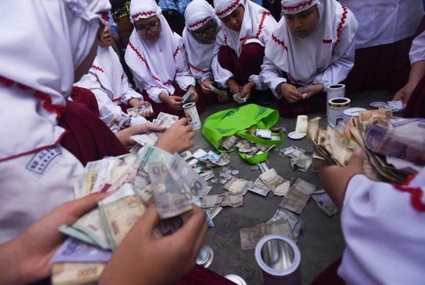 Sangu Lebaran Untuk Dhuafa. Sejumlah murid SD Al Falah Surabaya menghitung uang tabungan selama libur Lebaran ketika hari pertama masuk sekolah di halaman Sekolah mereka, Surabaya, Jawa Timur, Senin (27/7).