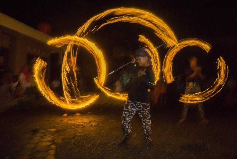 Santri memainkan atraksi tongkat api atau 'abid-abidan' pada perayaan hari santri nasional, di Pondok Pesantren Ath-Tohirriyah Karang Salam, Kedung Banteng, Banyumas, Jateng, Kamis (20/10).