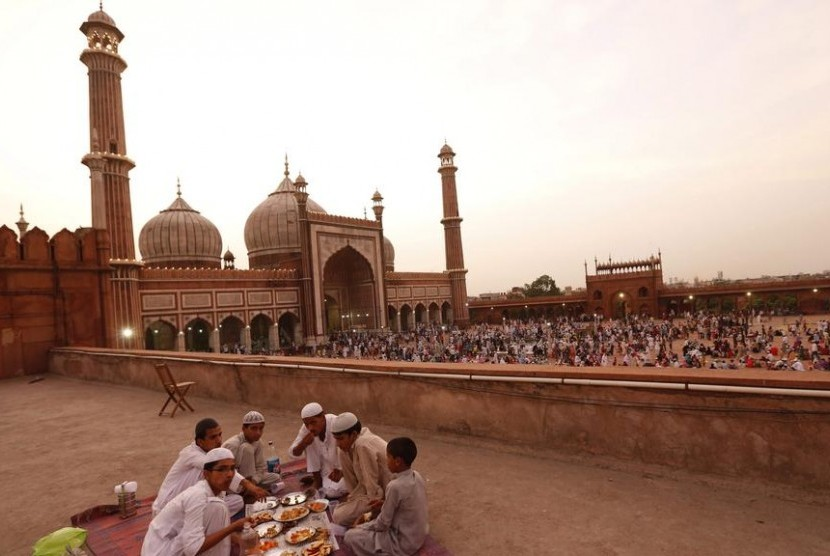 Satu keluarga menggelar tikar di atas ubin Masjid Jama di India untuk berbuka puasa.