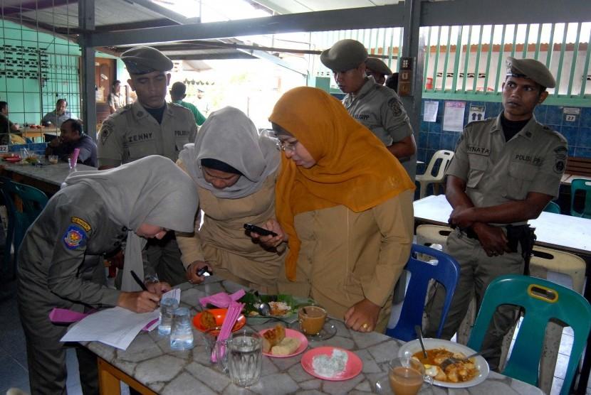 Satuan Polisi Pamong Praja (Satpol PP) mencatat identitas (KTP) dua orang PNS (kanan) yang terjaring saat razia disiplin di salah satu warung kopi.