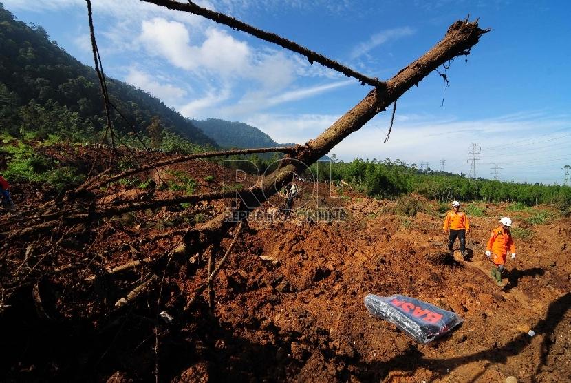 Sebuah alat berat mengevakuasi material longsor di Kampung Cibitung, Desa Margamukti, Pangalengan, Kabupaten Bandung, Jawa Barat, Rabu (6/5).  (Republika/Septianjar Muharam)
