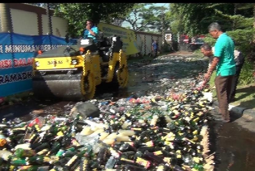 Sebuah alat berat, sedang memusnahkan ribuan botol miras (ilustrasi)