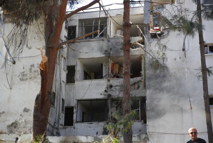Sebuah apartemen hancur akibat roket yang ditembakkan pasukan Palestina di Kota Ashkelon, Selasa (13/11) waktu setempat. Israel dan Palestina bersepakat untuk melakukan gencatan senjata.