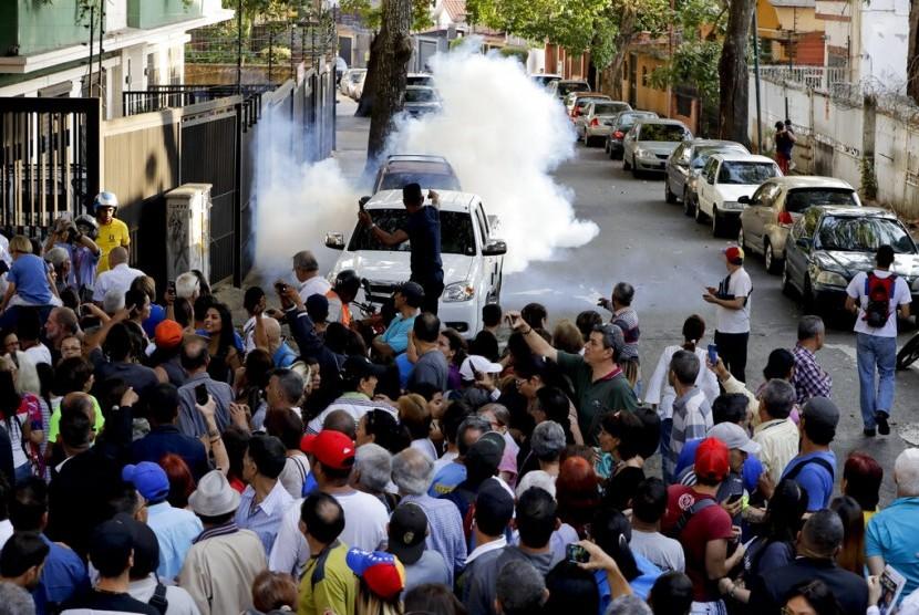 Sebuah gas air mata yang dilempar orang tak dikenal meledak di tengah kerumunan pendukung pimpinan oposisi Venezuela Juan Guaido di Caracas, Venezuela, Senin (1/4).