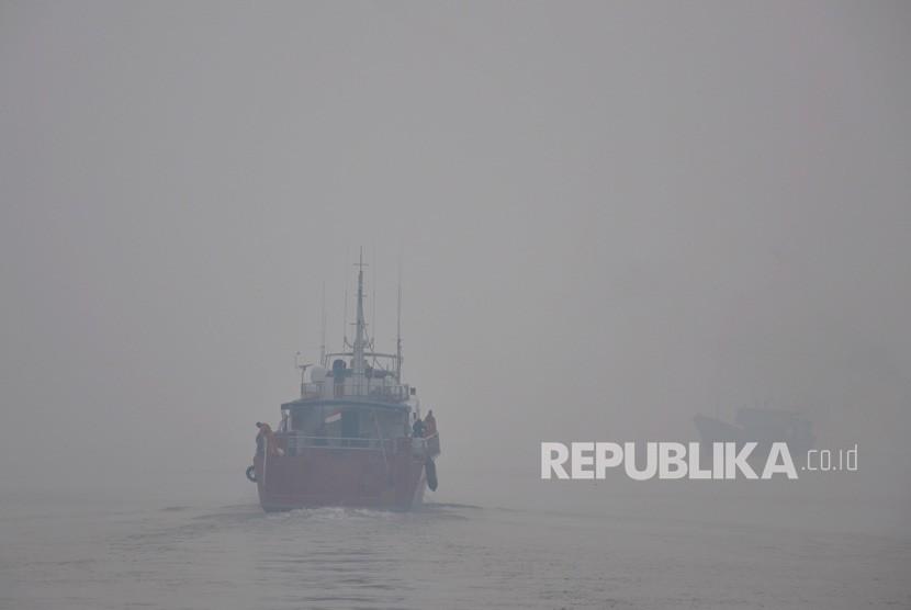 Sebuah kapal berlayar menembus kabut asap di pelabuhan Dumai, Riau, Selasa (3/9/2019).