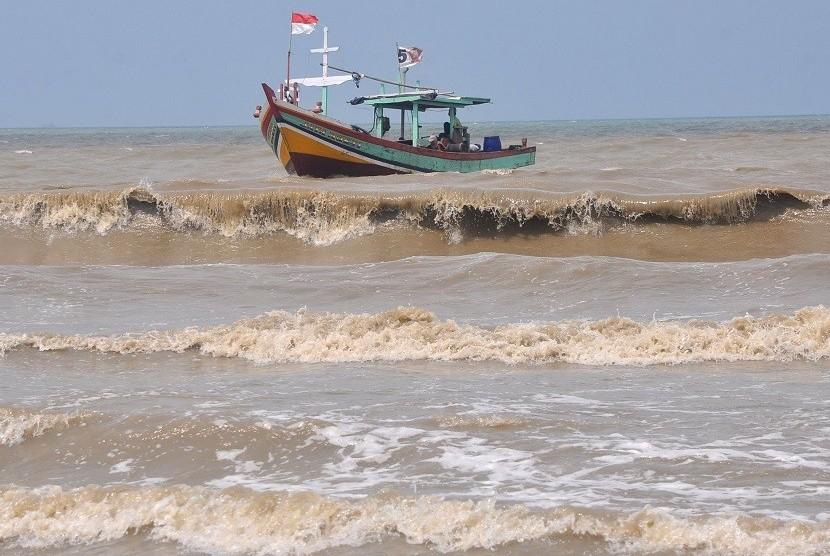 Sebuah kapal nelayan menerjang ombak usai melaut di laut jawa, Tegal, Jateng, Jumat (27/1).