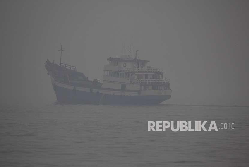 Sebuah kapal niaga melintas di perairan Dumai yang diselimuti kabut asap kebakaran hutan dan lahan di kota Dumai, Dumai, Riau, Rabu (29/8).