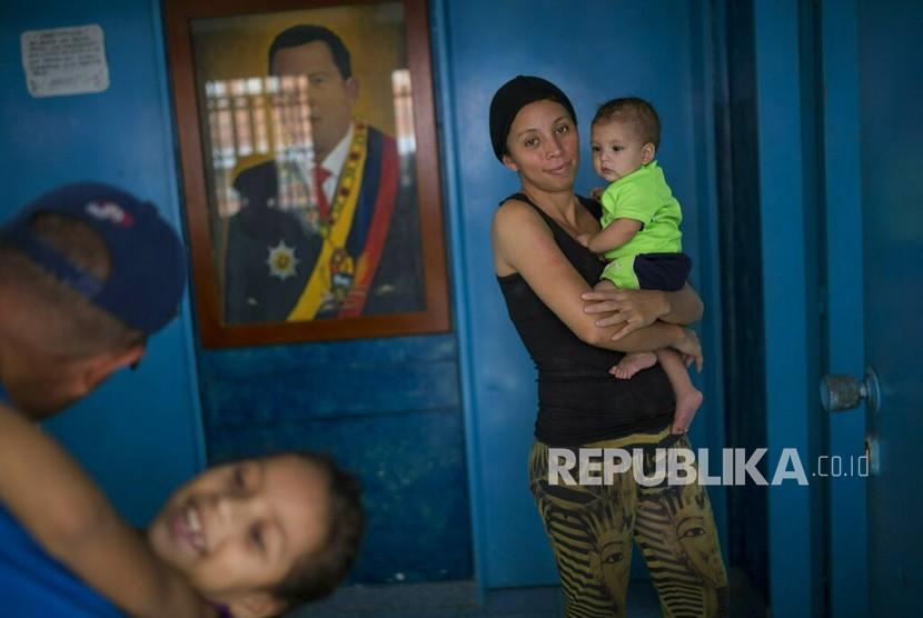 Sebuah keluarga bermain di ruang tamu rumah mereka, dihiasi dengan potret mendiang Presiden Venezuela Hugo Chavez, di Caracas, Venezuela, Kamis (7/2/2019).