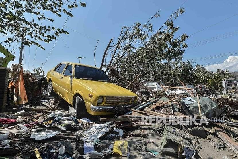 Sebuah mobil berada di reruntuhan bangunan yang hancur akibat tsunami pascagempa di wilayah Talise, Palu Barat, Sulawesi Tengah, Ahad (30/9).