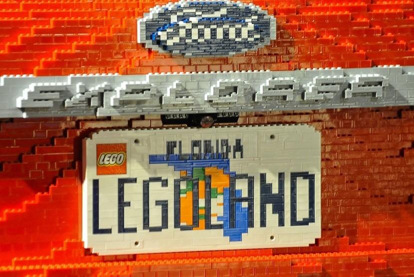 Sebuah mobil yang dirakit dari mainan Lego dan diberi plat bertuliskan Legoland.
