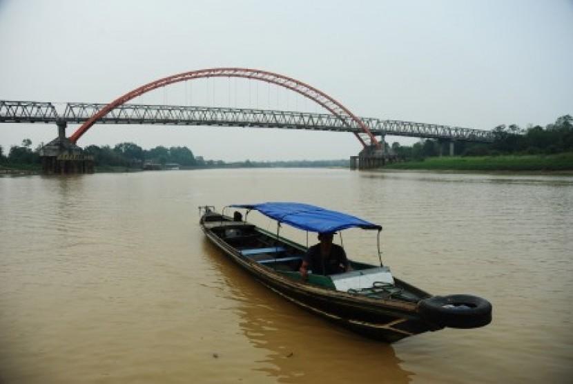 Sebuah perahu motor melintasi Sungai Kahayan yang diselimuti asap tipis di Palangka Raya, Kalimantan Tengah, Kamis (29/10).