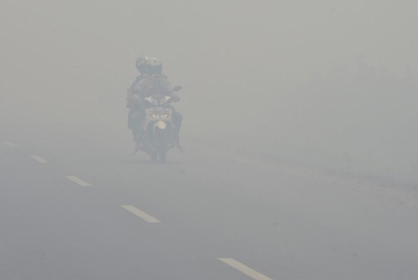 Sebuah sepeda motor menembus kabut asap ketika terjadi kebakaran lahan gambut di sekitar Pulang Pisau, Kalteng, Selasa (27/10).