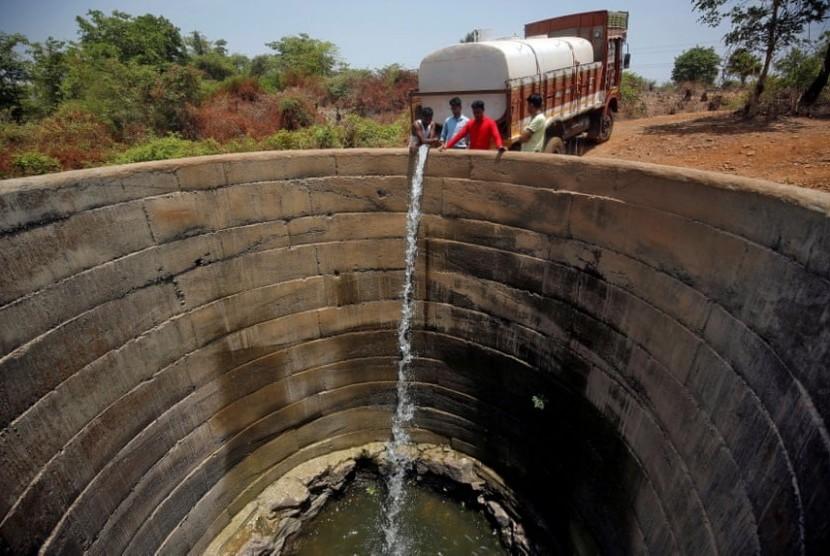 Sebuah sumur yang mengering diisi air dari truk di distrik Thane di negara bagian Maharashtra, India. India dilanda kekeringan.