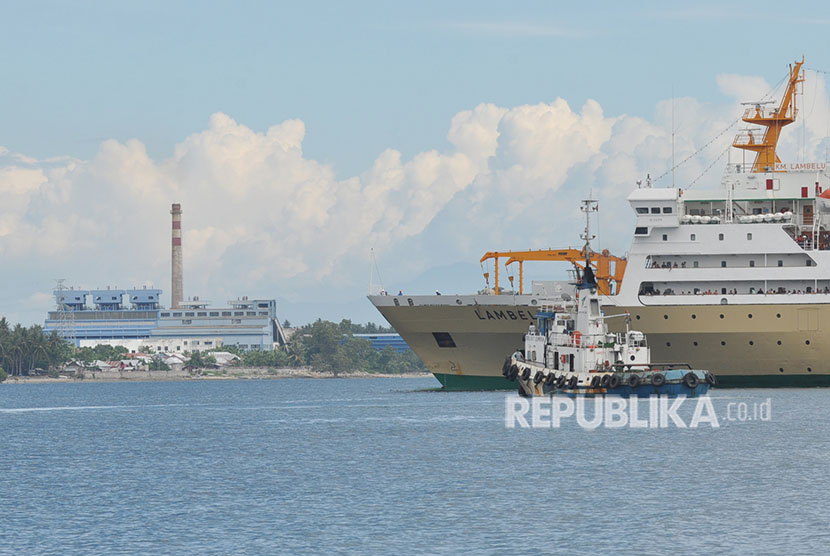 Sebuah tugboat dan kapal penumpang melintas dengan latar Pembangkit Listrik Tenaga Uap (PLTU) Mpanau di Kecamatan Tawaili, Palu Utara, Sulawesi Tengah, Sabtu (23/6).