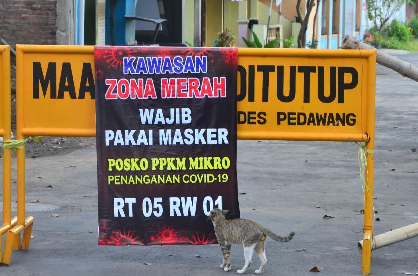 Seekor kucing mengendus poster bertuliskan kawasan zona merah COVID-19 di jalan desa yang ditutup akibat karantina wilayah di Desa Pedawang, Kudus, Jawa Tengah, Selasa (1/6/2021). Akibat lonjakan tajam kasus COVID-19 pascalebaran di kabupaten itu, sebanyak 42 desa masuk zona merah COVID-19 dan menerapkan aturan Pemberlakuan Pembatasan Kegiatan Masyarakat (PPKM) skala mikro untuk mencegah penularan COVID-19.