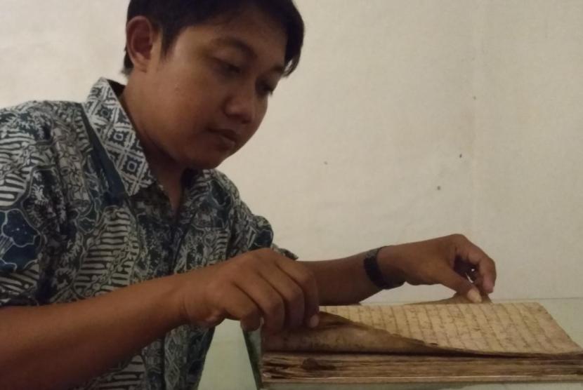 Sejarawan dan dosen Ilmu Sejarah IAIN Syekh Nurjati Cirebon, Tendi sedang membuka manuskrip Babad Sejarah Cirebon di Keraton Kacirebonan.