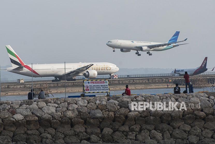 Sejumah wisatawan menyaksikan pergerakan pesawat di landasan pacu Bandara Ngurah Rai dari Pantai Patra Bali, Kuta, Selasa (15/5).