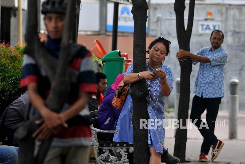 Sejumlah aktivis melakukan aksi peluk pohon di trotoar Jalan Jenderal Sudirman, Jakarta Pusat, Jumat (22/9).