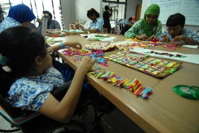 Sejumlah anak berkebutuhan khusus merangkai kalung berbahan manik-manik pada pelajaran keterampilan di Jakarta.