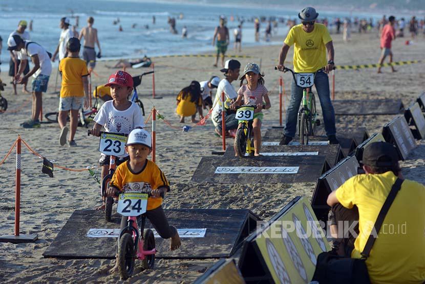 Sejumlah anak bermain balap sepeda dalam rangkaian Festival Pantai Kuta, Bali, Jumat (14/10). Festival yang digelar selama 3 hari tersebut menampilkan kesenian lokal, wisata kuliner dan berbagai kompetisi lainnya yang melibatkan para wisatawan dan pengunju