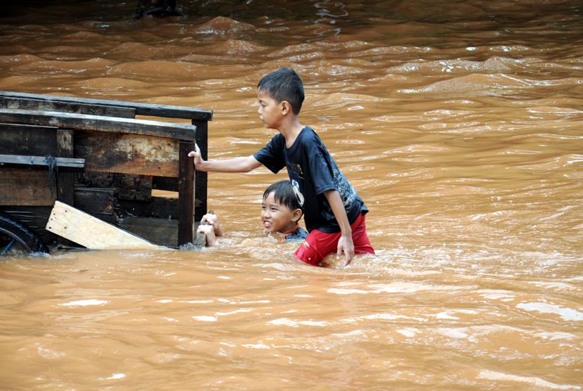 Sejumlah anak bermain di genangan air banjir di depan Perumahan Green Garden, Jakarta Barat, Rabu (11/2).  (foto : MgROL_34)