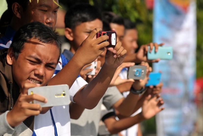 Sejumlah anak mengoperasikan telepon genggam saat menunggu bus yang membunyikan klakson telolet melintas di jalur Pantura, Brebes, Jawa Tengah, Rabu (21/12).