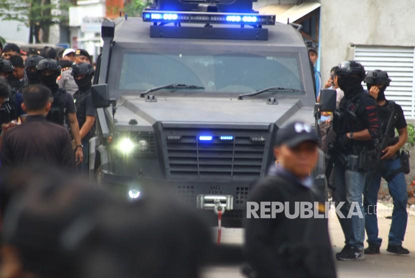 Sejumlah anggota Densus 88 menjaga ketat kendaraan taktis yang membawa tiga orang terduga teroris setelah penggerebekan di Gempol, Tangerang, Banten, Rabu (16/5).