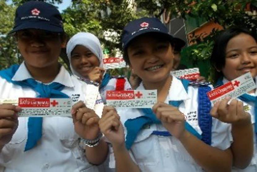 Sejumlah anggota Palang Merah Remaja menunjukkan lambang PMI saat memperingati Hari Ulang Tahun ke-66 Palang Merah Indonesia di Bandung, Jawa Barat.