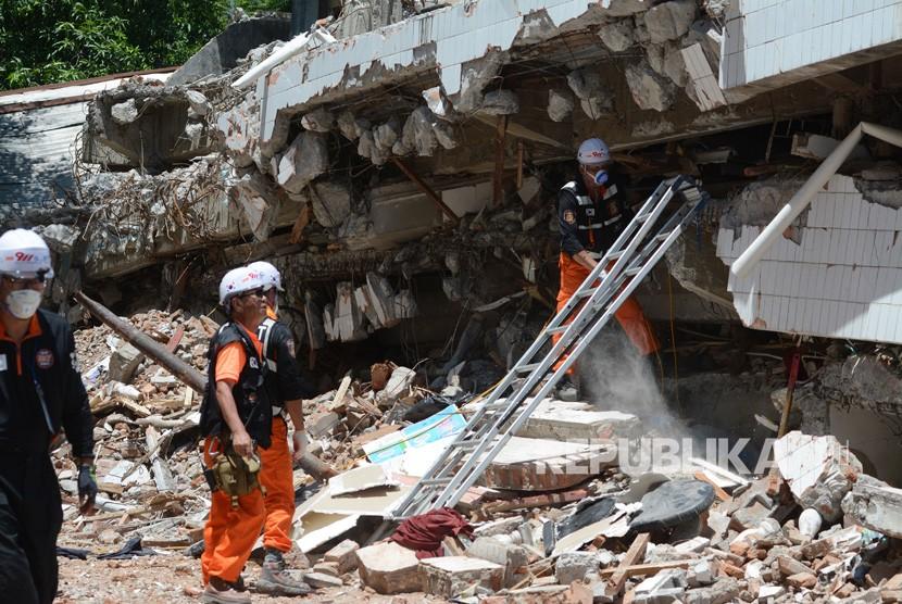 Sejumlah anggota Tim SAR Korea Selatan berusaha mengevakuasi korban gempa bumi yang tertimbun reruntuhan gedung Restoran Dunia Baru di Palu, Sulawesi Tengah, Senin (22/10/2018).