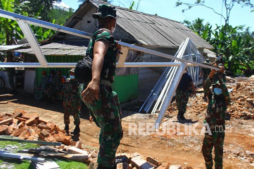 Sejumlah anggota TNI mengangkat rangka atap baja ringan yang akan digunakan untuk membangun rumah semi permanen di Jogomulyan, Malang, Jawa Timur (ilustrasi)