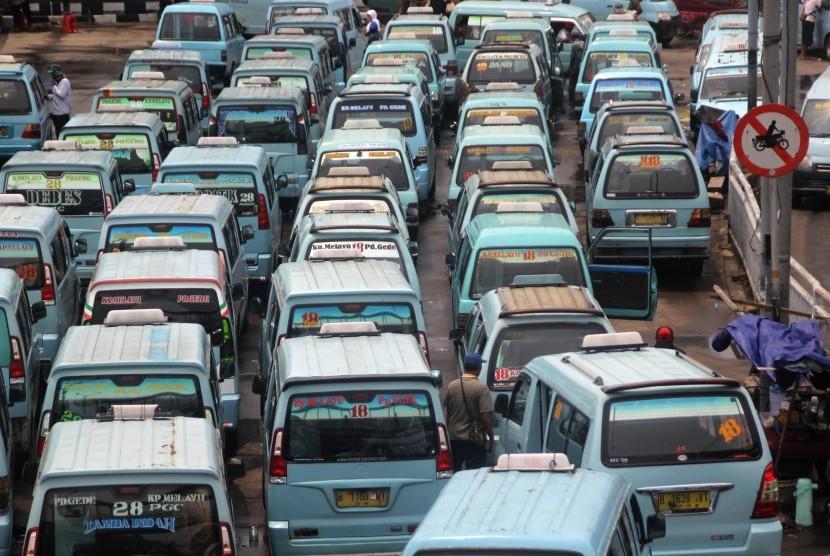 Sejumlah angkutan umum jenis mikrolet beroperasi menunggu penumpang di kawasan Kampung Melayu, Jakarta, Senin (14/3).