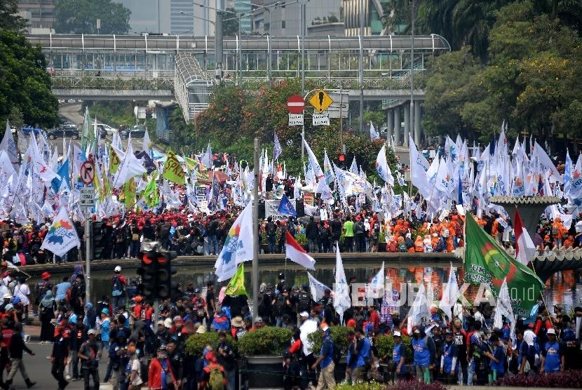 Sejumlah buruh menggelar aksi Hari Buruh Internasional di Jalan MH Thamrin, Jakarta, Pusat, Senin (1/5).