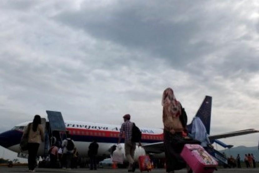 Sejumlah calon penumpang berjalan meuju pesawat komersil di Bandara Abdul Rachman Saleh, Malang , Jawa Timur, Senin (19/3). (Republika/Prayogi)