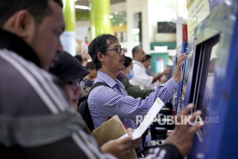 Sejumlah calon penumpang mencetak tiket kereta api di Stasiun Gambir, Jakarta, Rabu (21/6).