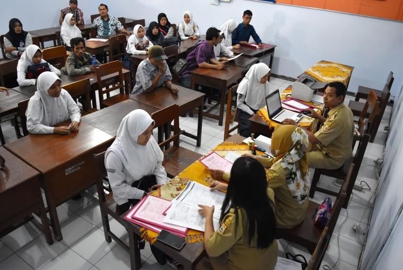 Sejumlah calon siswa menyerahkan berkas-berkas kelengkapan pendaftaran Penerimaan Peserta Didik Baru (PPDB) 2018 untuk diverifikasi di SMA Negeri 1 Ungaran, Kabupaten Semarang, Jawa Tengah, Senin (2/7).