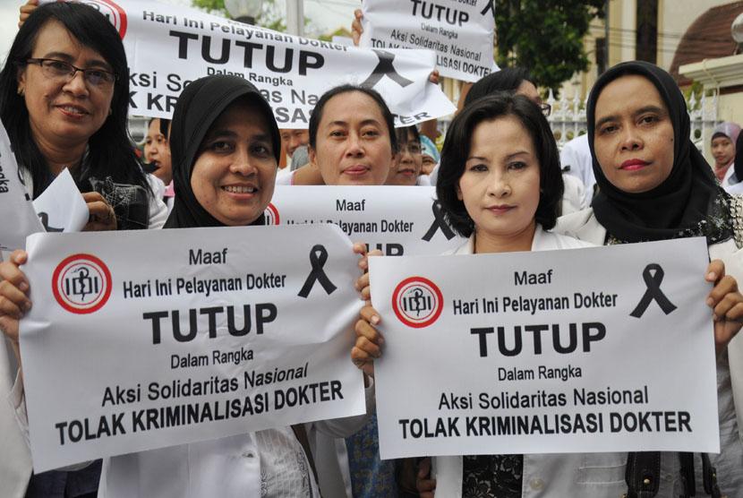 Sejumlah dokter membawa poster saat melakukan aksi solidaritas di depan Rumah Sakit Umum provinsi NTB di Mataram, Rabu (27/11).  (Antara/Ahmad Subaidi)
